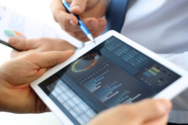 Kollegen arbeiten und analysieren von Finanzkennzahlen auf einem digitalen tablet – Foto