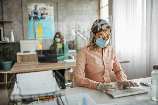 business colleagues working at office by maintaining social distance - business stock pictures, royalty-free photos & images