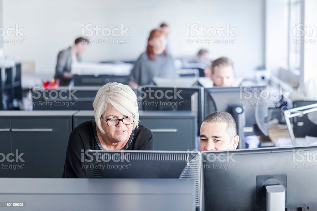 Business colleagues working in brightly lit office stock photo