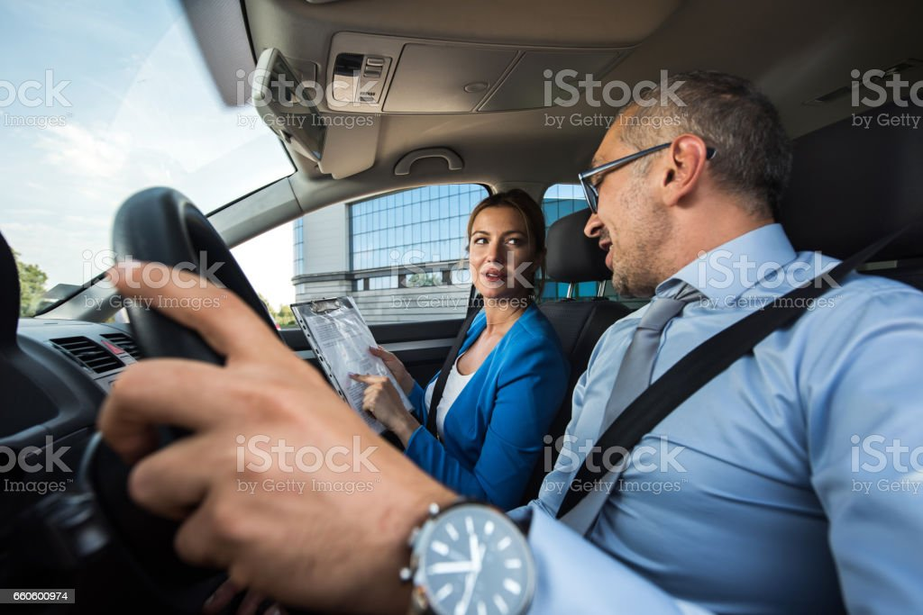 Business colleagues working on paperwork in the car. royalty-free stock photo
