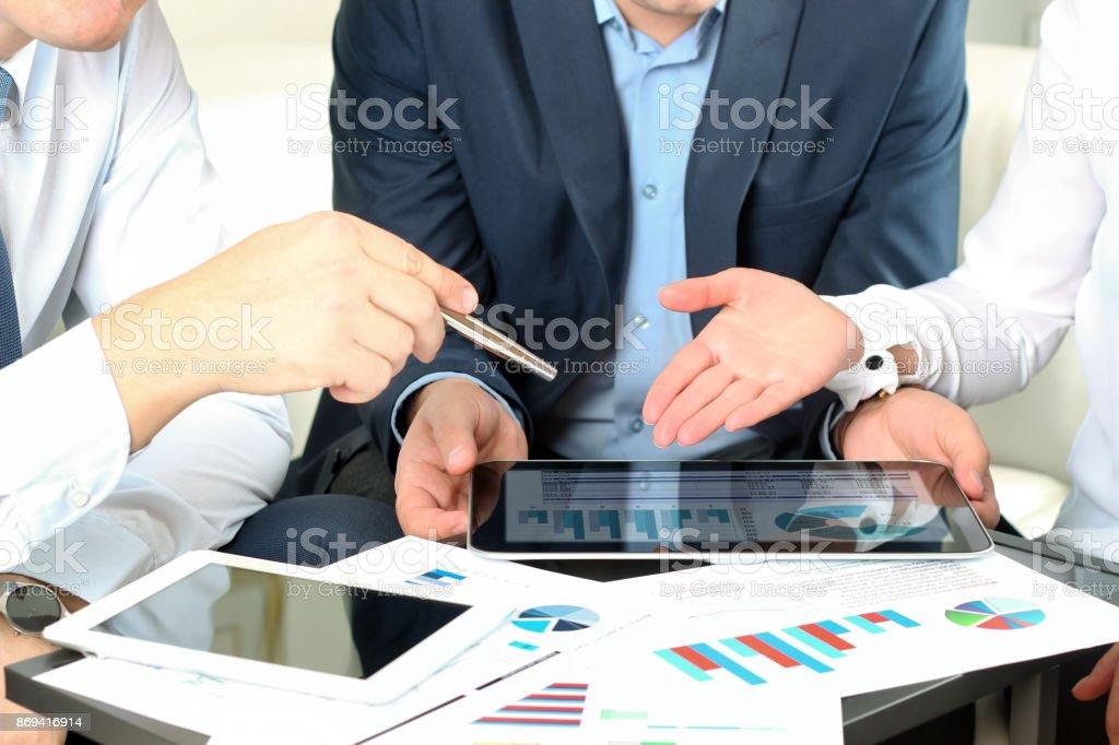 Kollegen zusammen arbeiten und analysieren von Finanzkennzahlen auf einem digitalen tablet – Foto