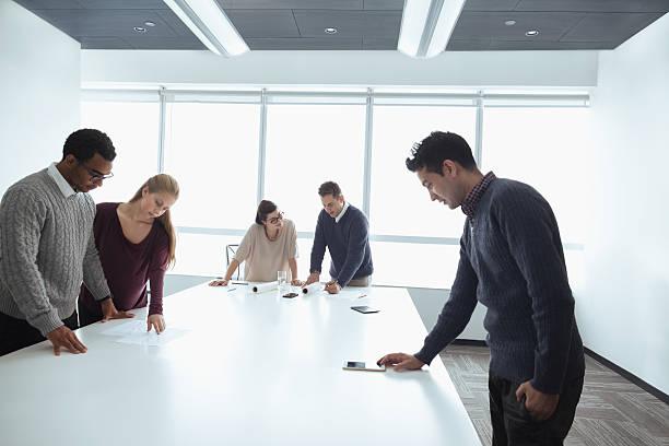 business colleagues working together in meeting room - oficina de empleo fotografías e imágenes de stock
