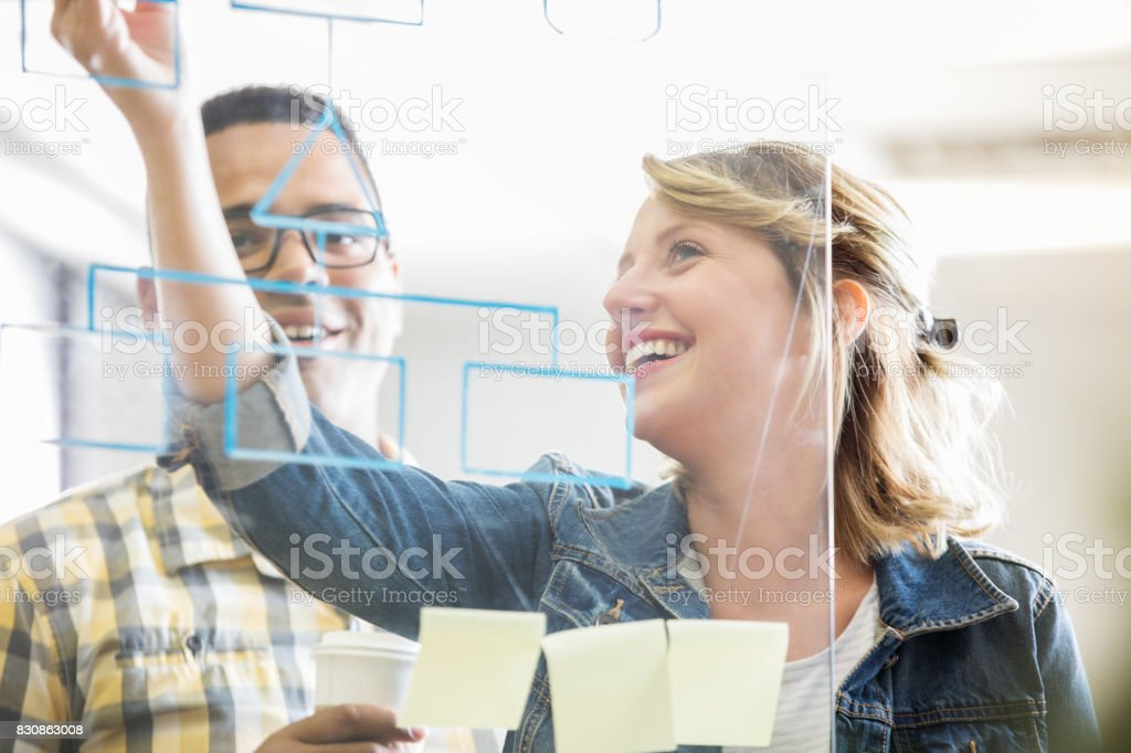 Business colleagues write ideas on transparent dry erase board stock photo