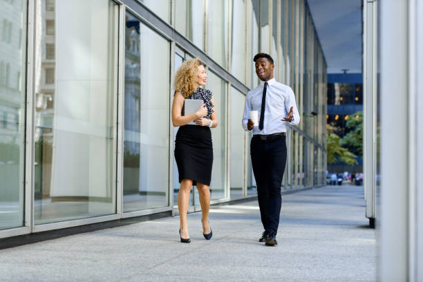 Business colleeagues walking along the office building stock photo