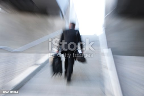 684803840istockphoto Business Commuter Rushing Upstairs, Carrying Suitcase 184118044