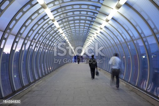 istock Business Commuters Rushing in Glass Walkway at Dusk 184594830