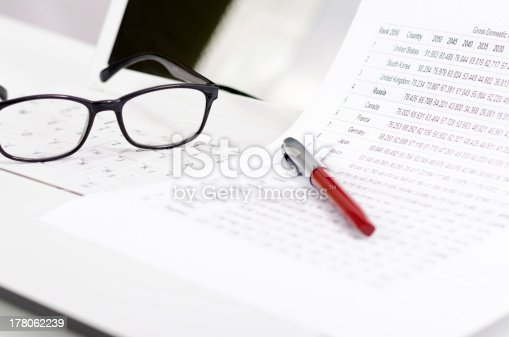1217929357 istock photo Business composition with laptop glasses pen and statistics sheets 178062239