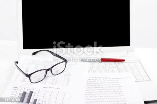 1217929357 istock photo Business composition with laptop glasses pen and statistics sheets 178720769