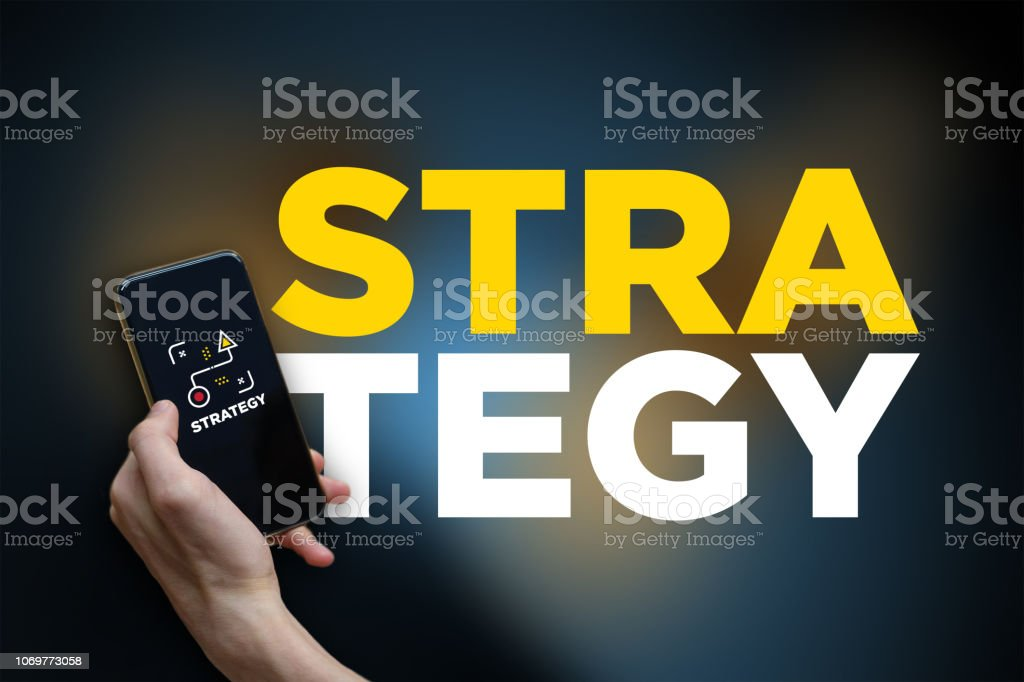 Business concept: Businessman hand holding a touch phone with strategy icon on the screen stock photo