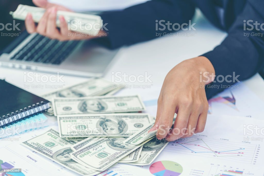 Business concept : Businesswoman counting The United States hundred-dollar bills with business charts , laptop and notebooks on the table stock photo