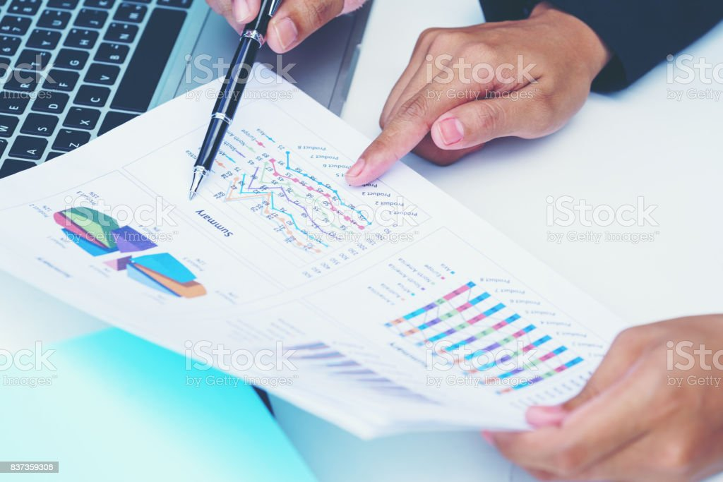 Business concept : Businesswoman pointing figure numbers of total sales comparing between global regions stock photo