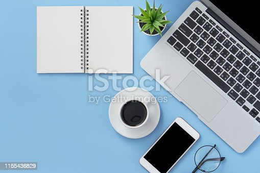 istock Business concept. Clean bright light blue office table desk, minimal style with laptop coffee and smart phone, copy space, top view, flat lay, mockup 1155436829