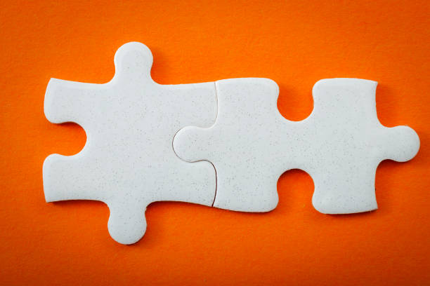 Business concept, connected puzzle pieces on orange background with copyspace stock photo