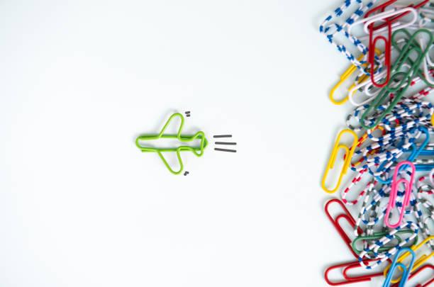 businessconcept voor gestapeld paperclip met een andere één groene vliegtuig paperclip groep gaat naar een andere richting als de leiding van een team - individualiteit stockfoto's en -beelden