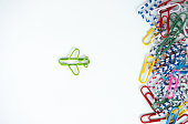 Business concept for group of stacked paperclip with another one green plane paperclip is point to another direction as a team leadership