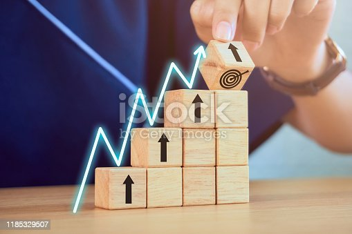 875531516istockphoto Business concept goal success. Close-up of hand holding wooden blocks stacking and growth graph on the table. 1185329507