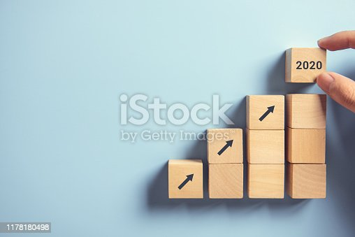 Close up man hand arranging wood block stacking as step stair on paper pink background. Business concept growth 2020 success process, copy space.