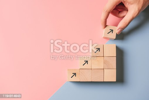 Business concept growth success process, Close up woman hand arranging wood block stacking as step stair on paper blue and pink background, copy space.
