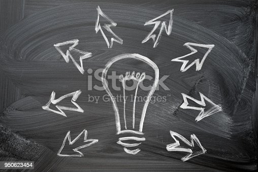 istock Business concept: Light Bulb icon hand chalk drawn on black chalkboard background and lot of arrows around, 950623454