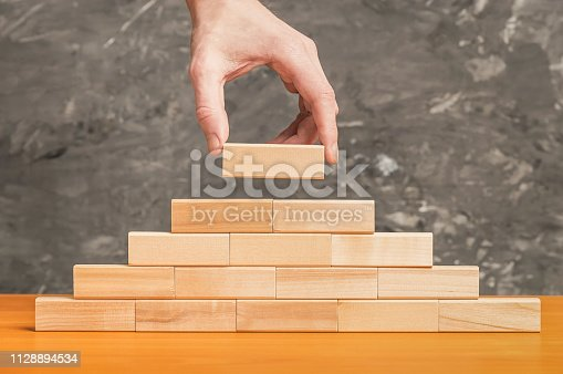 Business concept. Male hand puts a wooden cube