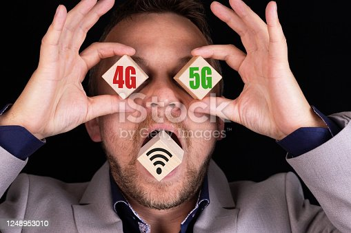 1152653473 istock photo Business concept of choosing and comparing 4G and 5G communication standards. The businessman holds cubes with the words 4G nano 5G on each cube, respectively. 1248953010