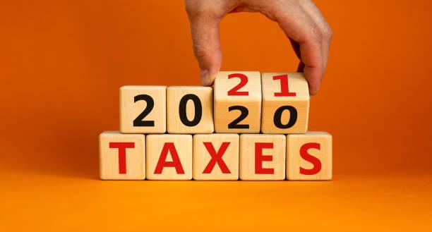 concetto aziendale di pianificazione 2021. la mano maschile capovolge i cubi di legno e cambia la scritta 'tasse 2020' in 'tasse 2021'. bellissimo sfondo arancione, spazio di copia. - tassa foto e immagini stock