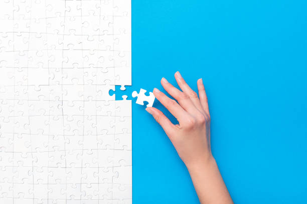 Business concept of white jigsaw puzzle. Hand put the last piece of jigsaw puzzle. Complete the mission. Business concept. puzzle pieces stock pictures, royalty-free photos & images
