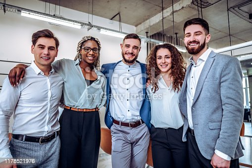 istock Business concept - partnership, unity, friendship.Young business team embracing standing together in an office. 1178521976