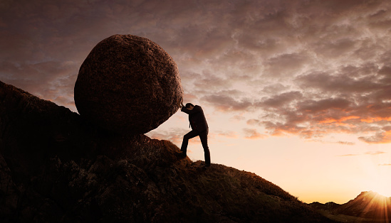Silhouette of young businessman pushing large stone uphill with copy space
