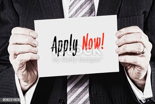 A businessman holding a business card with the words,  Apply Now, written on it.