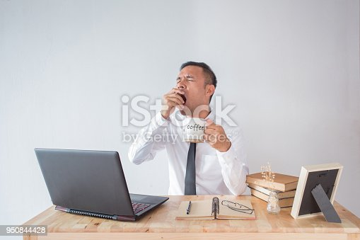 Young businessman yawning and drinking coffee to be energetic