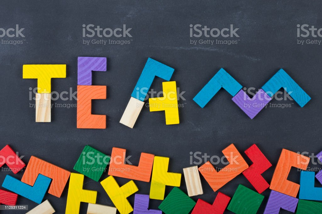 Business concept - team composed of color jigsaw blocks on the blackboard stock photo