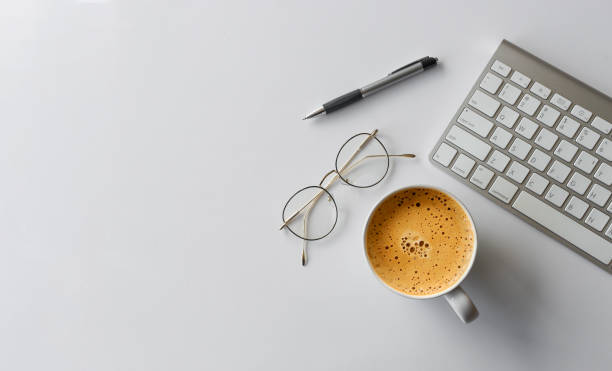 business concept. top view of office desk workspace with keyboard, pen, glasses and hot coffee cup on white table background. over light – zdjęcie