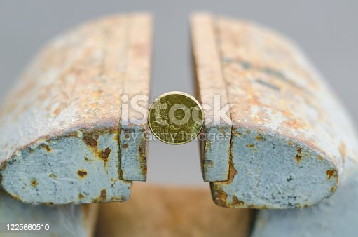 50 European cents are clamped in an old vice. Strong European currency