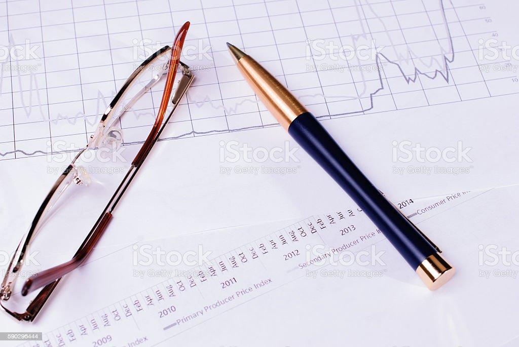 Business concept with Finance graphs, pen and glasses Стоковые фото Стоковая фотография
