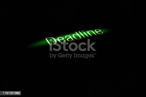 Business concept - word spelling in white letters for text Deadline in a line of light, dark around. The period of time during which something must be completed. Black background with copy space.
