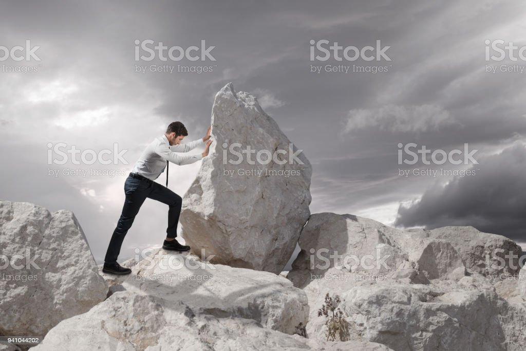 Business concept, Young businessman pushing large stone uphill with copy space stock photo