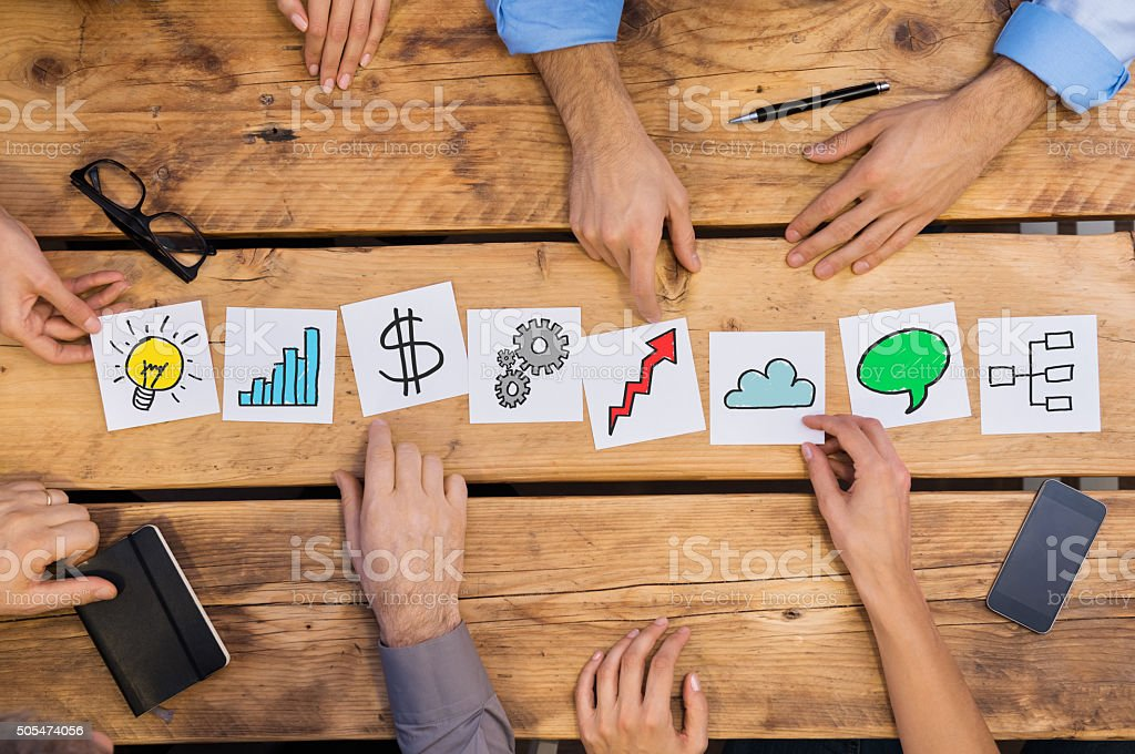 Business concepts on desk Businesspeople arranging different business concepts on wooden table. White cards strategy used by businesspeople. Business people brainstoring for new solutions while placing different cards in office. Achievement Stock Photo