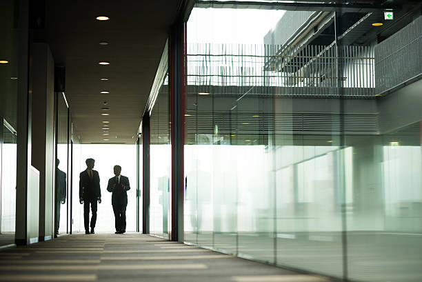 Business Concepts Silhouetted Businessmen discussing in the corridor of a modern office building only japanese stock pictures, royalty-free photos & images