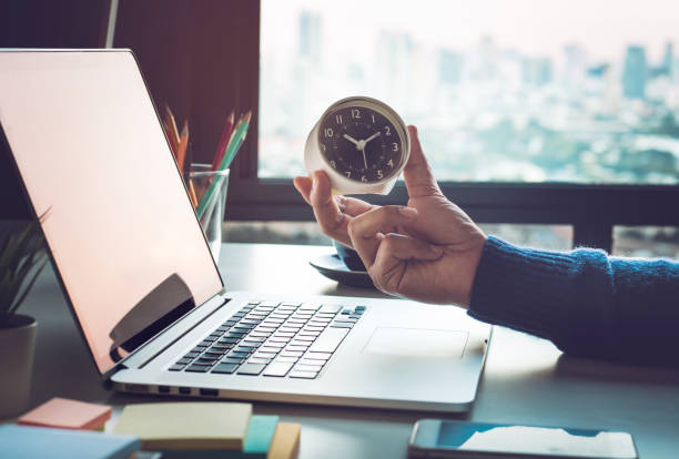 koncepcje biznesowe z biznesmenem trzymającym zegar na laptopie komputerowym. do analizy inwestycji,oczekiwanie na sukces - czas zdjęcia i obrazy z banku zdjęć