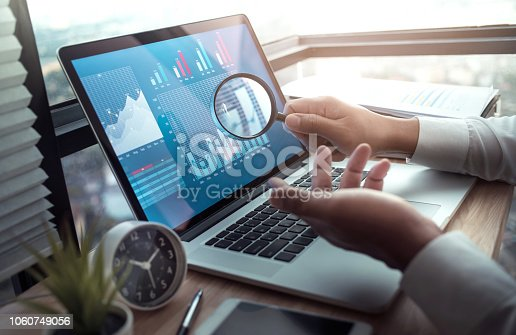 801895196 istock photo Business concepts with businessman holding magnifying glass with graph chart on computer laptop. 1060749056