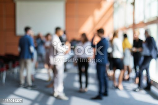 A blurred image of a group of business people attending a meeting
