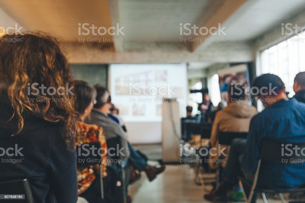 Business Conference Audience people sitting rear at the business seminar on the screen in Conference Hall. Adult Stock Photo