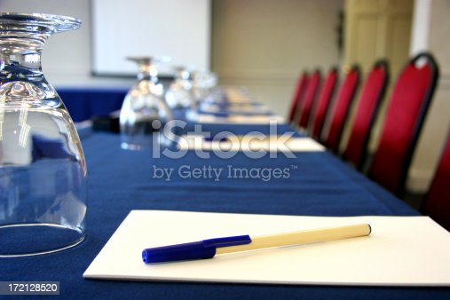 Business conference room with water glass, notepad, pens, chairs and a presentation screen. Room on notepad, screen, or pen for logo placement