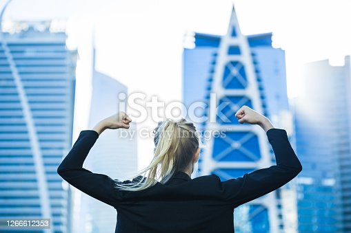 Career strength, motivation and success - Confident powerful young businesswoman flexing both arms in front of a modern city with high-rise buildings.
