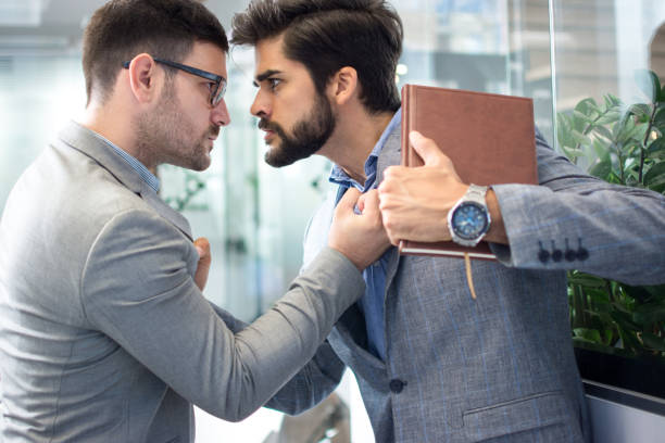 Business conflict between two business men in formal-wear in office. Boss and employee with aggressive expression fight. stock photo