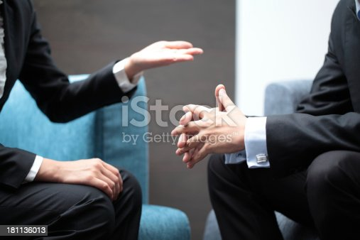 Hand gestures of a businesswoman and businessman in meeting.