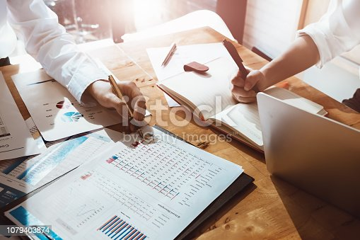950986656istockphoto business consulting or finance budget plan, business advisor holding pen pointing to explain method profit with business owner use pen write to notebook and use laptop computer. 1079403874