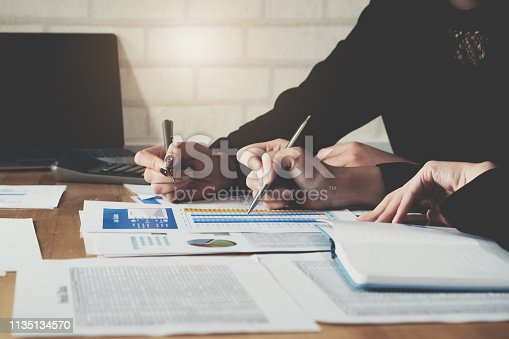 950986656istockphoto business consulting or finance budget plan, business advisor holding pen pointing to explain method profit with business owner use pen write to notebook and use laptop computer. 1135134570