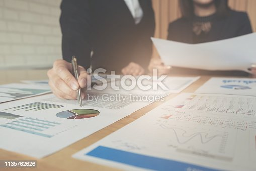 950986656istockphoto business consulting or finance budget plan, business advisor holding pen pointing to explain method profit with business owner use pen write to notebook and use laptop computer. 1135762626